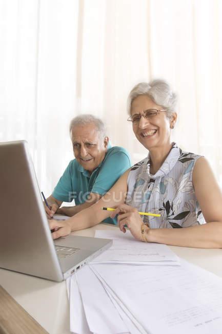 Couple de personnes âgées faisant le travail du papier — Photo de stock