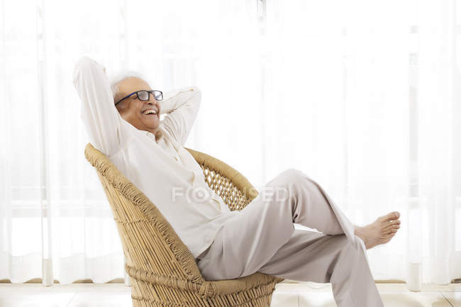 Homme senior souriant assis — Photo de stock