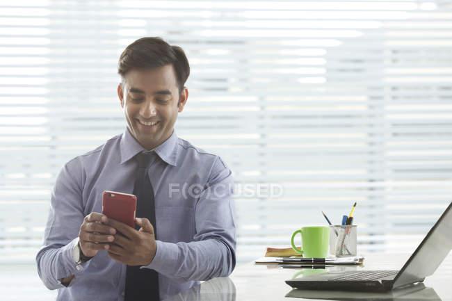 Homme d'affaires en regardant téléphone mobile — Photo de stock