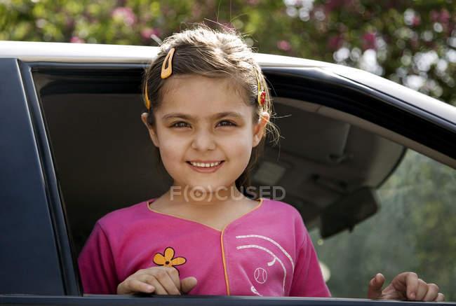 Jeune fille regarde par la fenêtre de la voiture — Photo de stock