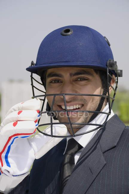 Executive in cricket helmet — Stock Photo