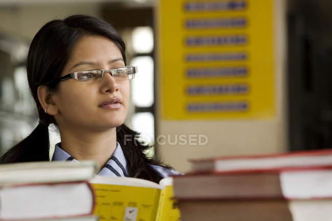 Ragazza in una biblioteca scolastica — Foto stock