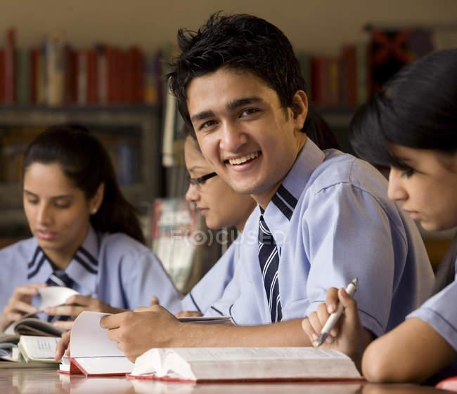 Étudiants assis dans une bibliothèque de l'école — Photo de stock