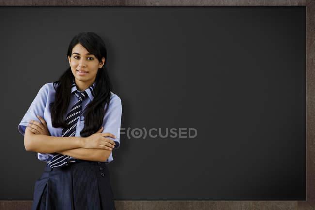 Jeune fille devant un tableau noir — Photo de stock