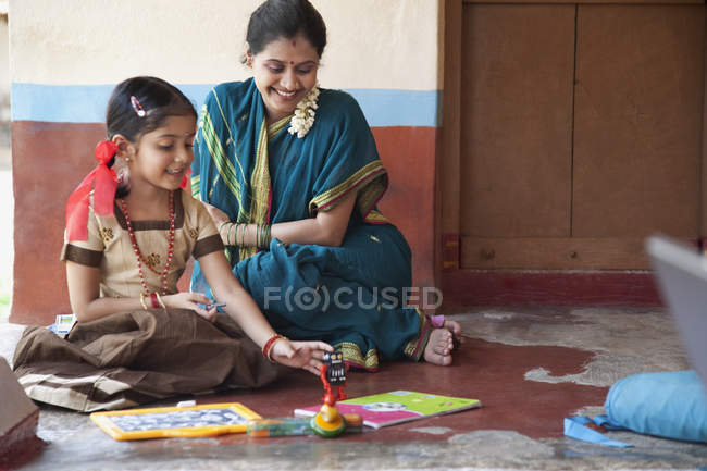 Little girl studying with mother — Stock Photo