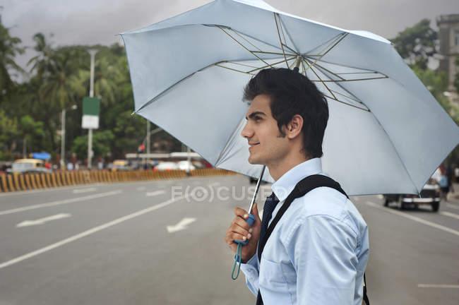 Businessman with an umbrella — Stock Photo