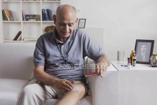 Человек, применяя мазь на колено — стоковое фото