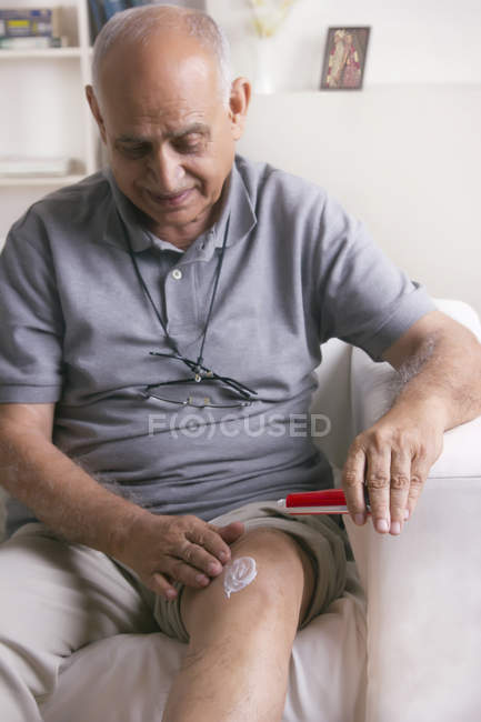 Man applying ointment on knee — Stock Photo