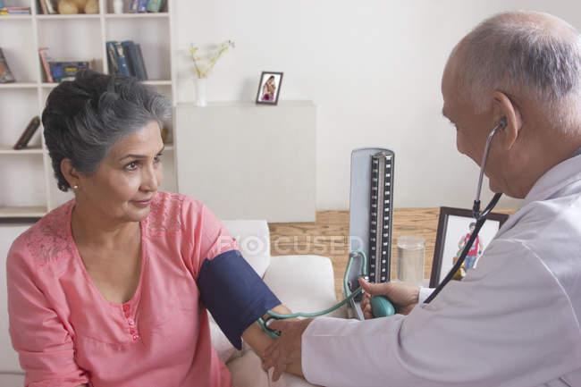 Mulher recebendo sua pressão arterial verificada — Fotografia de Stock