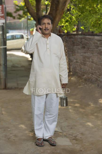 Uomo che tiene il contenitore di latte — Foto stock