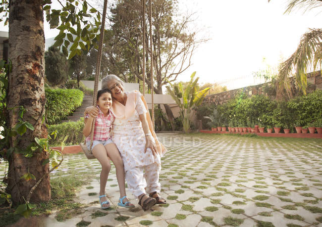 Grandmother and granddaughter sitting on a swing — Stock Photo