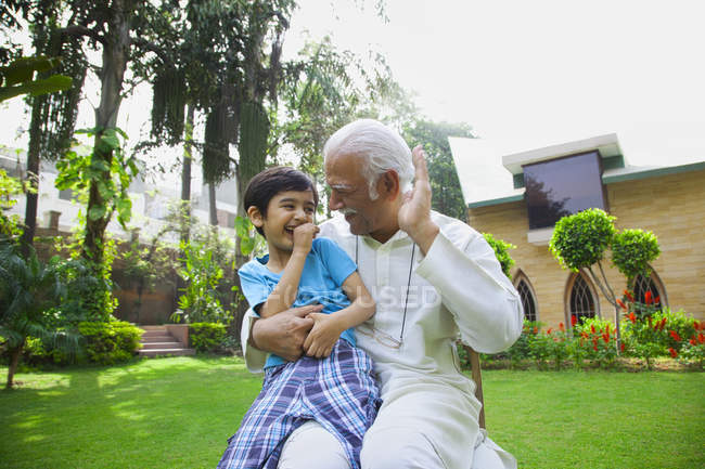 Grandfather and grandson in garden — Stock Photo