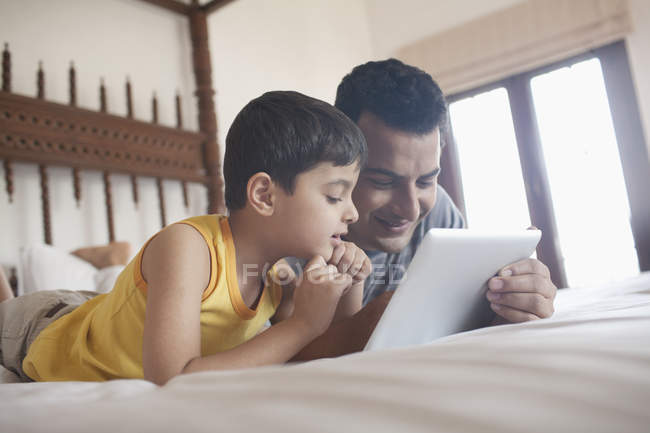 Padre e hijo en una tableta digital - foto de stock