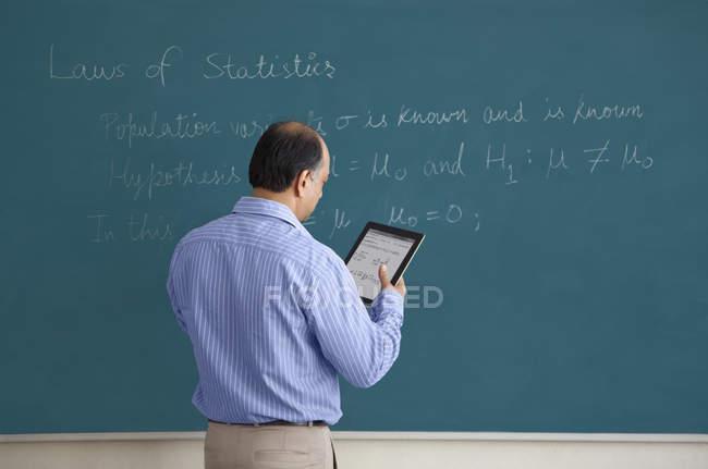 Enseignant à l'écriture de la tablette numérique — Photo de stock