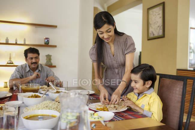 Mãe, colocando comida — Fotografia de Stock