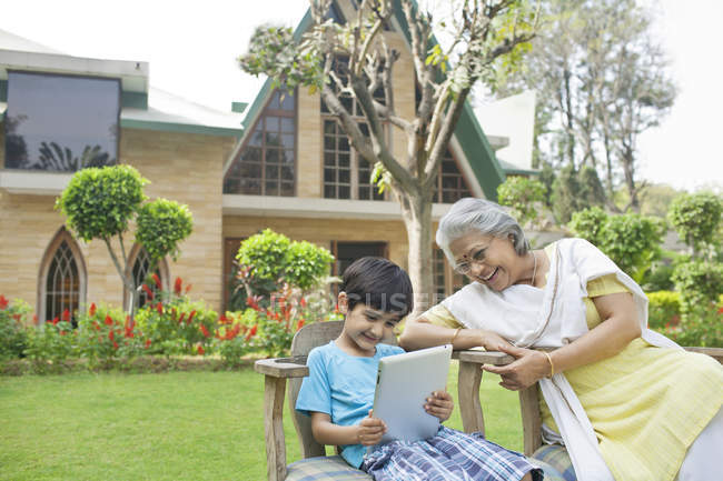 Grandmother and grandson with digital tablet — Stock Photo