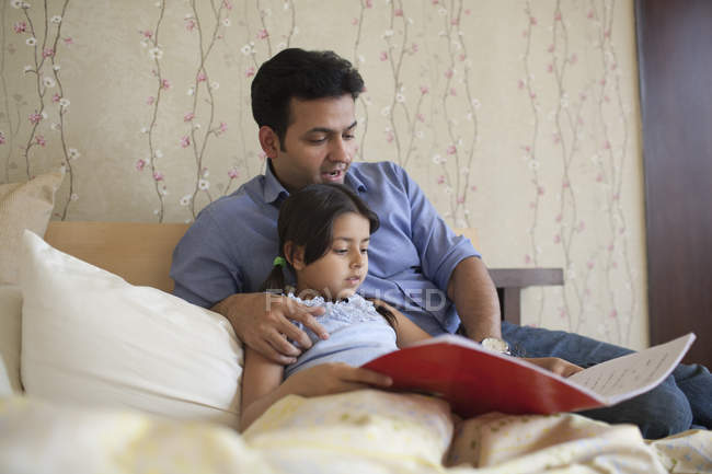 Father reading story to daughter — Stock Photo