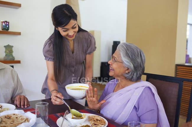 Mulher servindo a mãe em lei — Fotografia de Stock