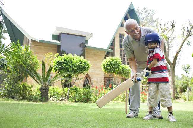 Boy playing cricket with grandfather — Stock Photo