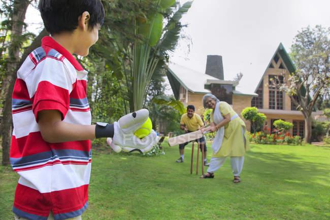 Молодой мальчик, играя крикет с бабушкой — стоковое фото