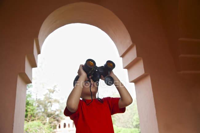 Boy looking through binoculars — Stock Photo