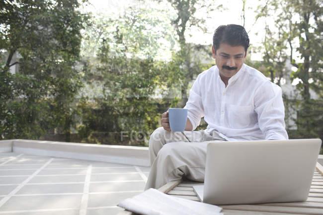 Homme avec ordinateur portable et tasse — Photo de stock