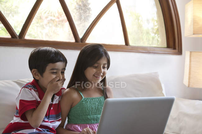 Hermano y hermana usando laptop - foto de stock
