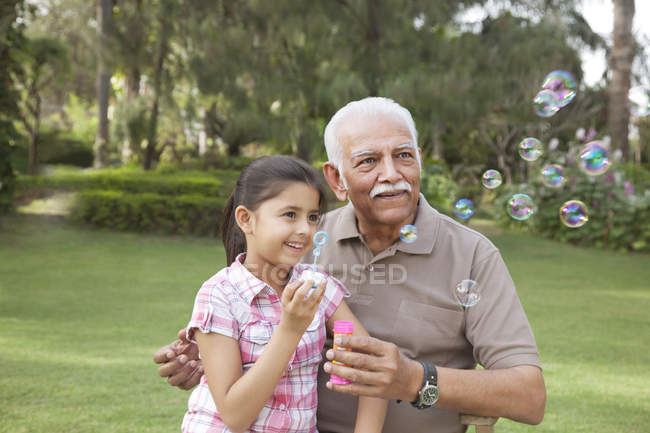 Little girl blowing bubbles — Stock Photo