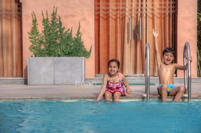 Kinder sitzen am Rand des Pools — Stockfoto
