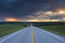 Nuages orageux sur route droite près de Water Valley, Alberta, Canada — Photo de stock
