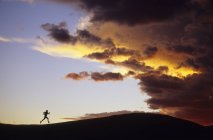 Силует жінка працює на хребті по відношенню до шторм на захід сонця, Каньонлендс Національний парк, Моава, штат Юта, США — стокове фото