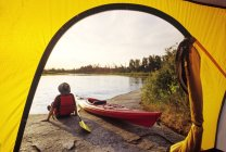 Rear view of male tourist by tent along Whiteshell River, Whiteshell Provincial Park, Manitoba, Canada. — Stock Photo