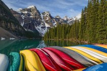 Colorful canoes stacked at pier at Moraine Lake, Banff National Park, Alberta, Canada — Stock Photo