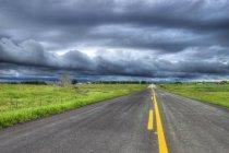 Autopista y nubes de tormenta cerca de Cochrane, Alberta, Canadá - foto de stock