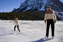 Mother and daughter skating at ice rink at Lake Louise, Banff National Park, Alberta, Canada. — Stock Photo