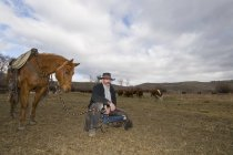 Cowboy with horse watching herd of cows on ranch near Merritt, British Columbia, Canada — Stock Photo