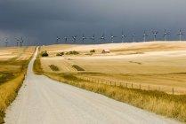 Stormy sky and turbines at road near Pincher Creek, Alberta, Canada — Stock Photo