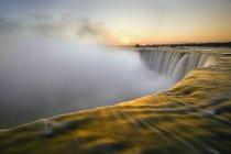 Vista de ángulo alto del agua corriente de las cataratas de la herradura al atardecer, Cataratas del Niágara, Ontario, Canadá - foto de stock