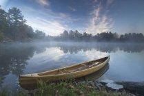 Moored wooden canoe at shore on Muskoka lake in Ontario, Canada — Stock Photo
