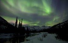 Aurores boréales au-dessus des montagnes et de la rivière Wheaton à l'extérieur de Whitehorse, Yukon, Canada . — Photo de stock