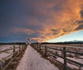 Cloudscape over McDougall Church in snow-covered meadow, Morley, Alberta, Canada — Stock Photo