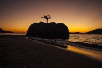 Силуэт женщины йогой на прибрежной скале на рассвете в Калимнос, Греция — стоковое фото
