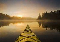 Kayak sur l'eau pendant le matin brumeux sur le lac des bois, nord-ouest de l'Ontario, Canada — Photo de stock