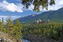 Здание отеля Fairmont Banff Springs Hotel всматриваясь от леса в национальном парке Банф, Альберта, Канада — стоковое фото