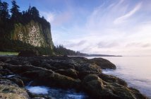 Tranquil scene of rocky Haida Gwaii coastline with Tow Hill on Graham Island at dusk, British Columbia, Canada. — Stock Photo