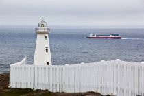 Lighthouse and passing cargo ship at Cape Spear, Newfoundland — Stock Photo
