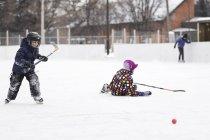 Хлопчики грають хокею відкритий каток — стокове фото