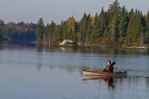Donna che gode della mattina in kayak sul lago di origine, Algonquin Park, Ontario, Canada. — Foto stock