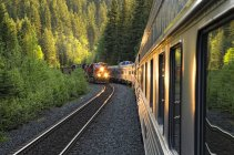 Eastbound freight train meeting westbound passenger train in British Columbia, Canada. — Stock Photo