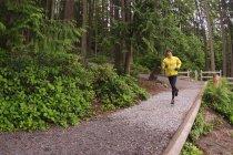 Mid adult man jogging on trail around Sasamat Lake, Belcarra Regional Park, Port Moody, British Columbia, Canada — Stock Photo